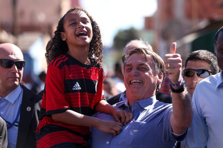 O presidente Jair Bolsonaro posa para fotos na cidade Estrutural, em Brasília, ao lado da menina Yasmin Alves, de 8 anos, pivô de desentendimento do presidente com a imprensa na semana passada