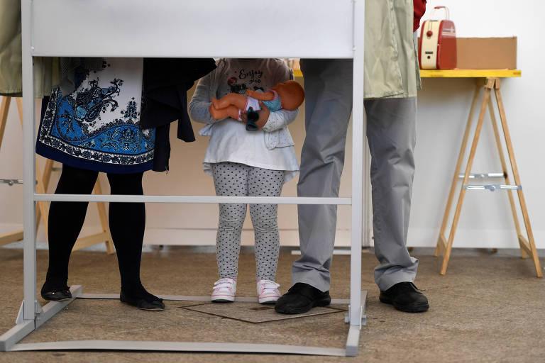 Menina acompanha os pais na votação das eleições parlamentares da Espanha, em Pola de Siero
