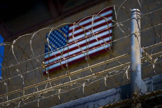 An American flag is seen through barbed wire at Guantánamo Bay, Cuba.