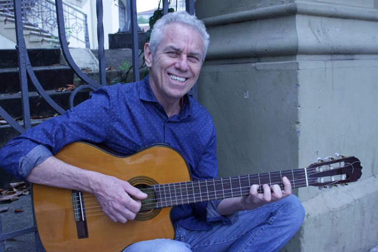 Com cabelos brancos e camisa social azul, cantor e compositor Roberto Riberti posa com violão para foto; na imagem, ele sorri, sentado, de costas para um portão