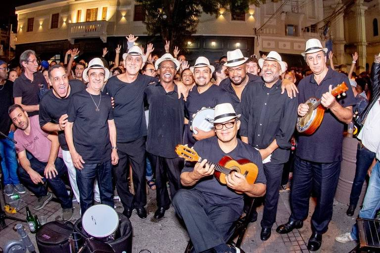 De camisetas e calças pretas de chapéus brancos, integrantes do Grupo Madeira de Lei posam abraçados e em pé, à exceção de um deles, em primeiro plano, agachado e segurando um cavaquinho