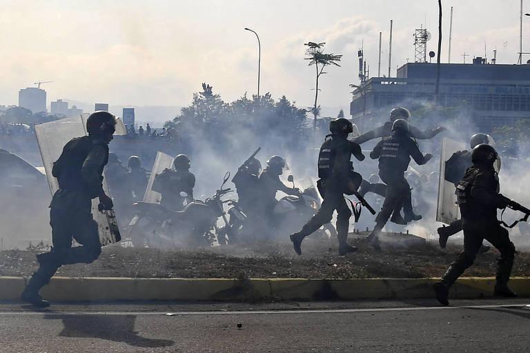 Guardas nacionais, leais a Maduro, fogem de tiros disparados por militares aliados a Guaidó