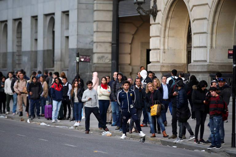 grande fila de pessoas num ponto de ônibus