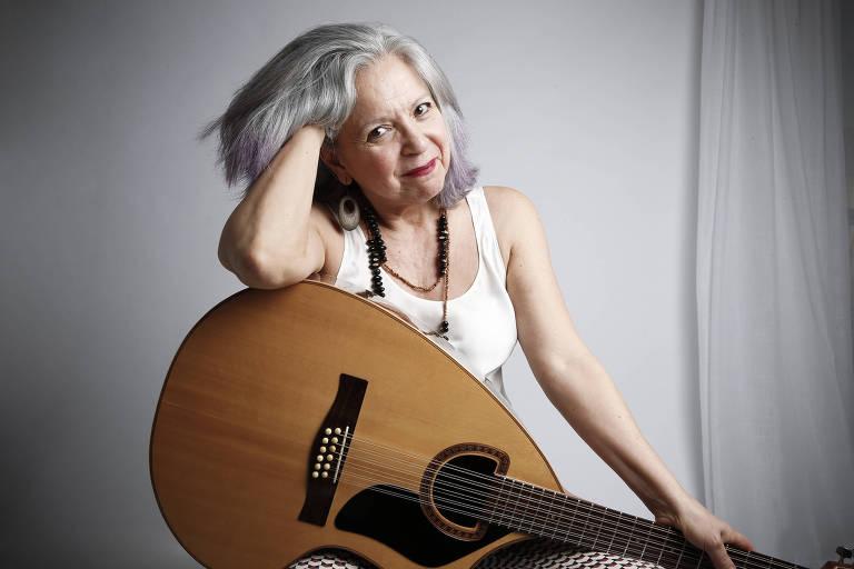Com a mão direita nos cabelos brancos, Tetê Espíndola posa sorrindo e sentada com o instrumento craviola no colo