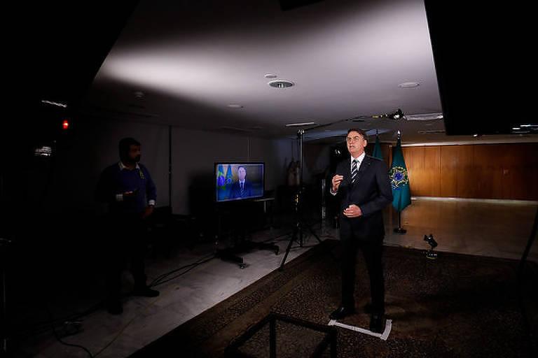 Presidente está em pé, em frente a câmera. Ele usa terno preto, gravata e camisa branca