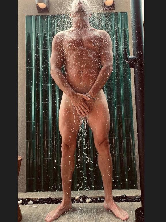 ator nu no chuveiro com as mãos nas genitais