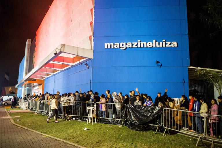 A foto mostra uma fila de consumidores esperando para entrar na loja da Magazine Luiza. Ao fundo, a loja aparece iluminada, com o logo da empresa na parede do lado direito.