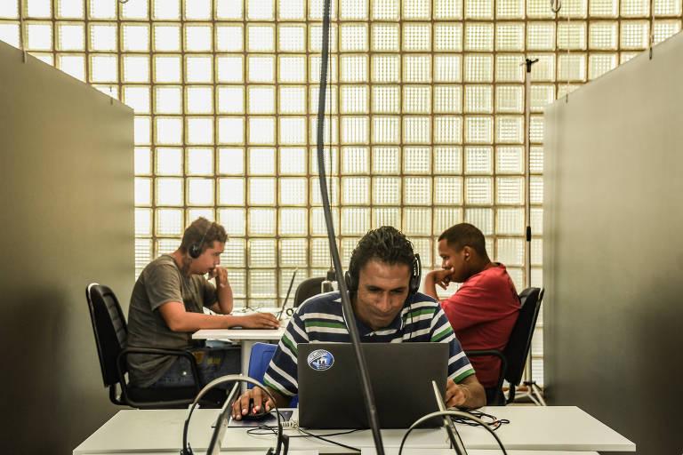 Homem de camisa de manga comprida, listrada, está em frente a um notebook navegando na internet. Ele usa fone de ouvidos. Atrás dele, outros dois homens estão sentados e navegando