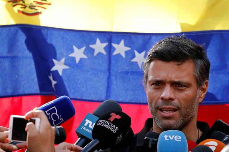 O líder opositor Leopoldo López fala com jornalistas na frente da residência do embaixador espanhol em Caracas, com a bandeira da Venezuela ao fundo