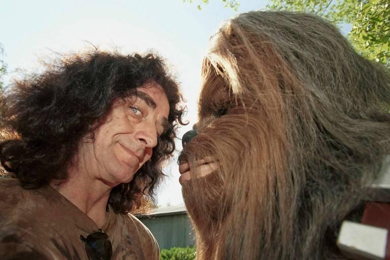 O ator Peter Mayhew, à esq., com sujeito sob a fantasia de Chewbacca