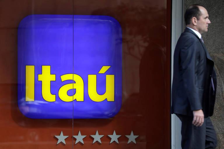Um homem de terno passa na frente de uma propaganda com o logo do Itaú no Rio de Janeiro.