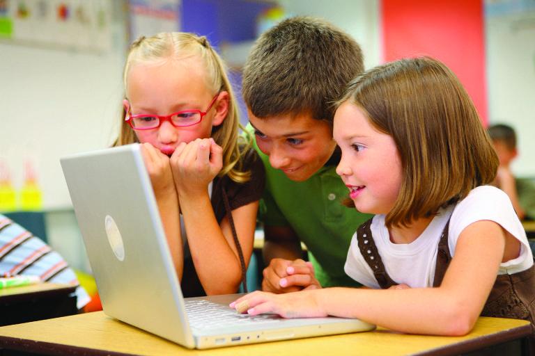 Três crianças brancas estudam em frente a computador da Apple