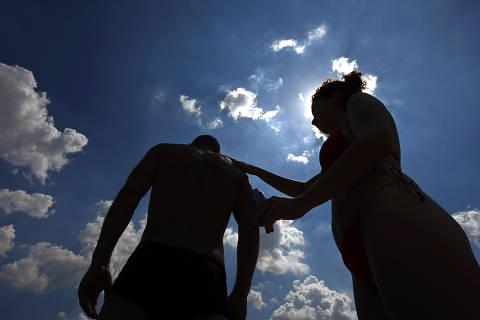 SÃO PAULO, SP, 22.02.2010 - Casal aplica filtro solar no Parque do Ibirapuera, em São Paulo. A radiação solar chega a níveis extremos no Brasil. A proteção é indispensável. Além do filtro solar, é recomendado usar barreiras físicas, como boné ou guarda-chuva. (Foto: Almeida Rocha/Folhapress)