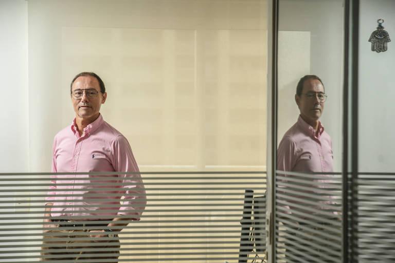 Sergio Aronis atrás de um vidro com linhas horizontais até a altura do peito