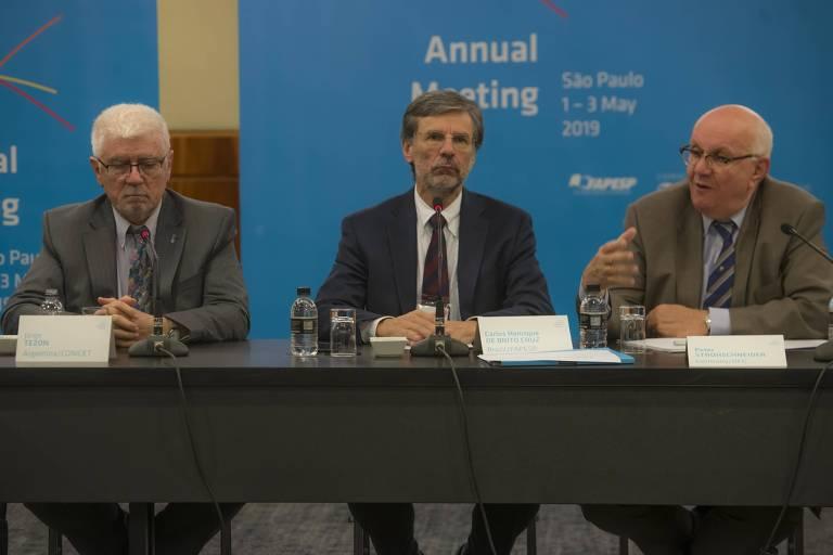 Três representantes de instituições científicas sentados em uma mesa em frente a cartaz de evento