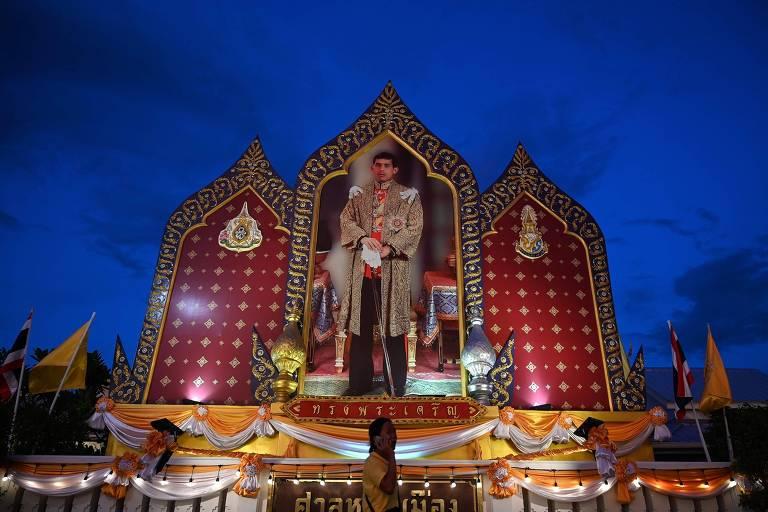 Mulher passa por retrato do rei Maha Vajiralongkorn do Grande Palácio Real, antes de sua coração, em Bancoc