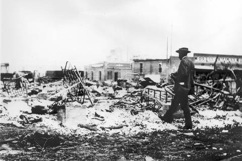 Photograph of an African-American man with a camera looking at the skeletons of iron beds which rise above the ashes of a burned-out block after the Tulsa Race Riot, Tulsa, Oklahoma, 1921. (Photo by Oklahoma Historical Society/Getty Images)    *** SOLICITADA PELO DAIGO / CLAUBER ***