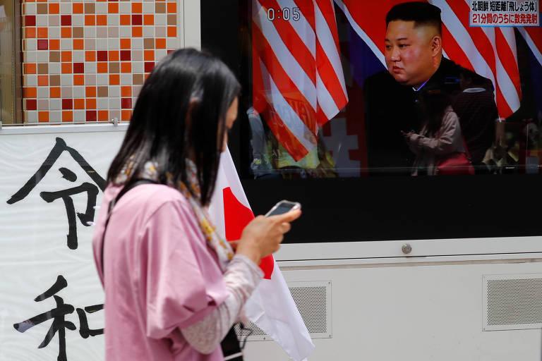 Mulher passa por TV em Tóquio, no Japão, que fala sobre Pyongyang ter lançado vários mísseis não identificados no mar na manhã de sábado (noite de sexta no Brasil)