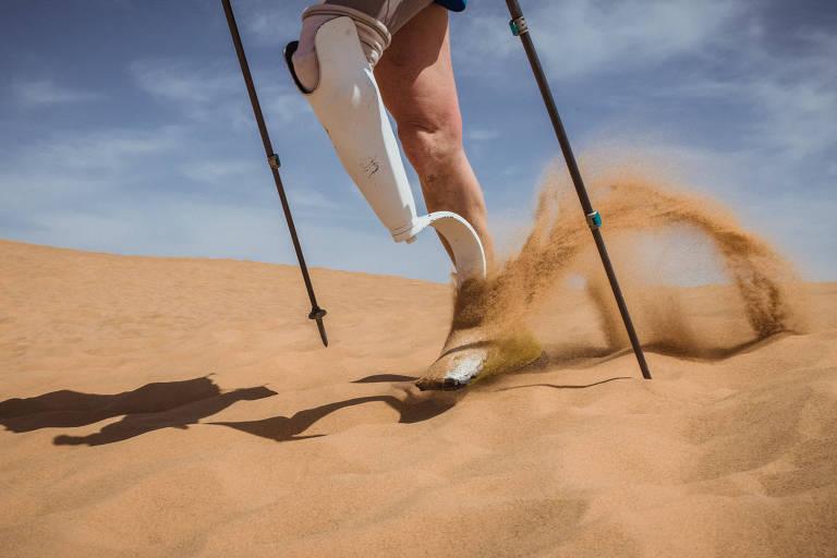 Perna humana ao lado de prótese para amputados, na areia
