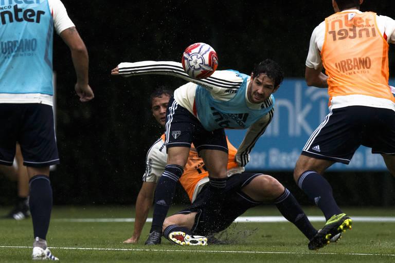 Durante treino do São Paulo, Anderson Martins, de colete laranja, dá um carrinho para tentar desarmar Alexandre Pato, de colete azul,, que se desequilibra e fica com as costas curvadas