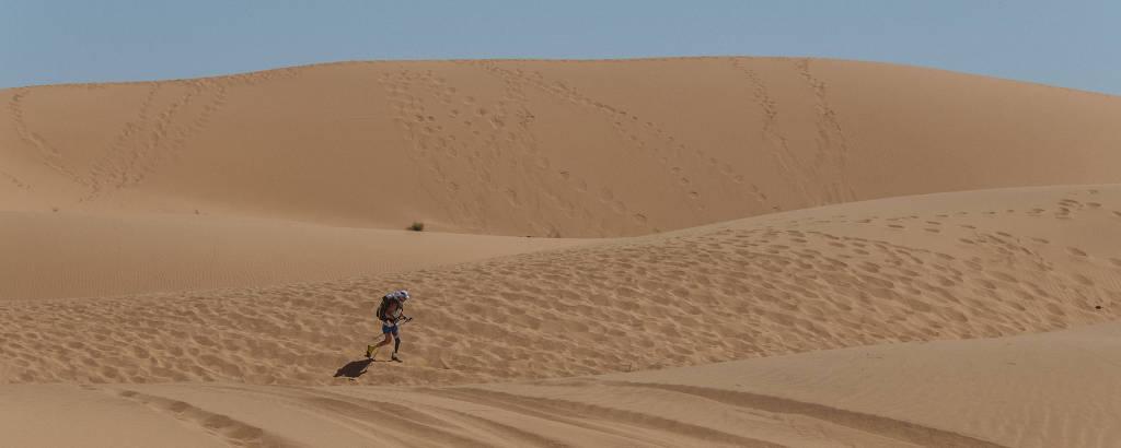 Mulher com prótese na perna caminha em deserto