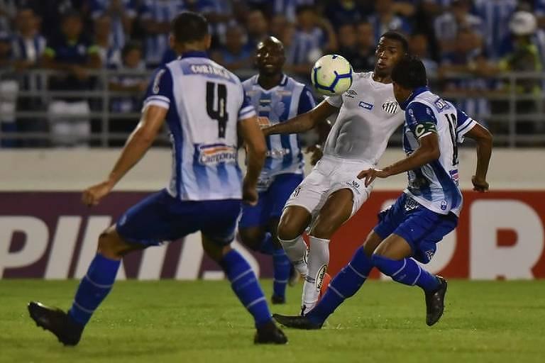 Com a bola à sua frente na altura do peito, o volante santista Jean Lucas tenta passar por tripla marcação do CSA no estádio Rei Pelé