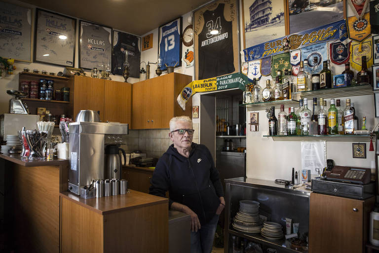 Giannis Tsiggas no seu café, que fica em frente à quadra onde Antetokounmpo aprendeu a jogar, com camisas do astro grego na parede