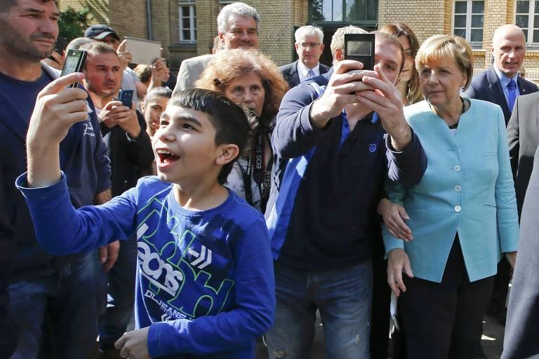 A chanceler alemã Angela Merkel tira foto com migrantes da Síria e do Iraque em Berlim