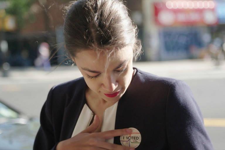 """Alexandria Ocasio-Cortez ajusta broche com os dizeres """"eu votei"""" em suéter azul que está vestindo"""