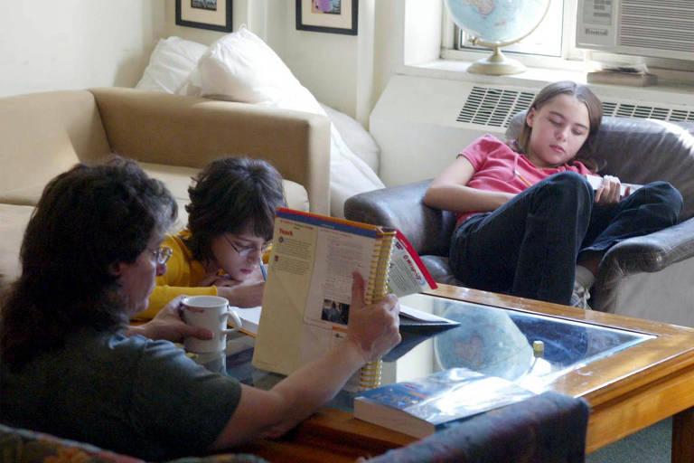 Penny Kjellberg, que educa seus filhos em casa, durante aula de matemática com os gêmeos Caroline, ao centro, e Jessica
