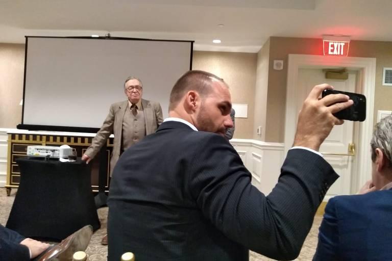 Eduardo de costas tira foto com o celular