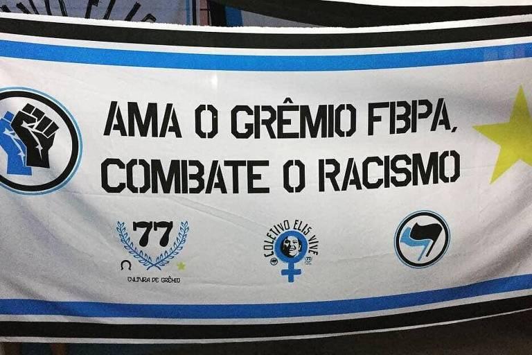 """Bandeira de torcida do Grêmio contra o racismo escrito: """"Ama o Grêmio FBPA, combate o racismo""""."""