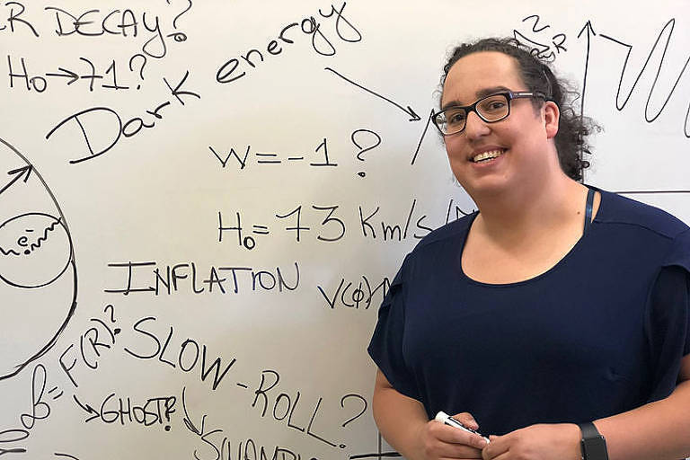 A física e mulher trans brasileira Vivian Miranda, 33, que recebeu o Leona Woods Award, ao lado de uma lousa