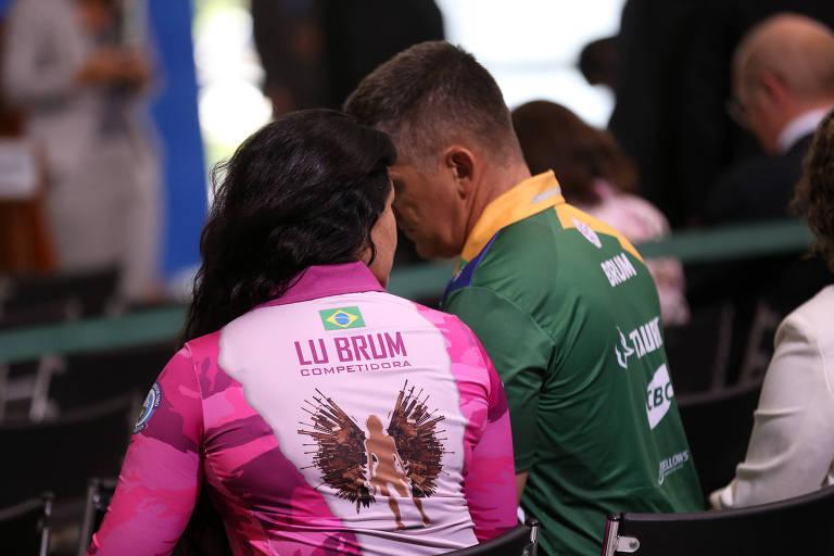 """A mulher, de cabelos compridos, está com uma camiseta cor-de-rosa com o nome """"Lu Brum"""" escrito nas costas, parte de seu uniforme de tiro. Ela está sentada ao lado do marido, que veste uma camiseta verde e amarela, também de uniforme"""