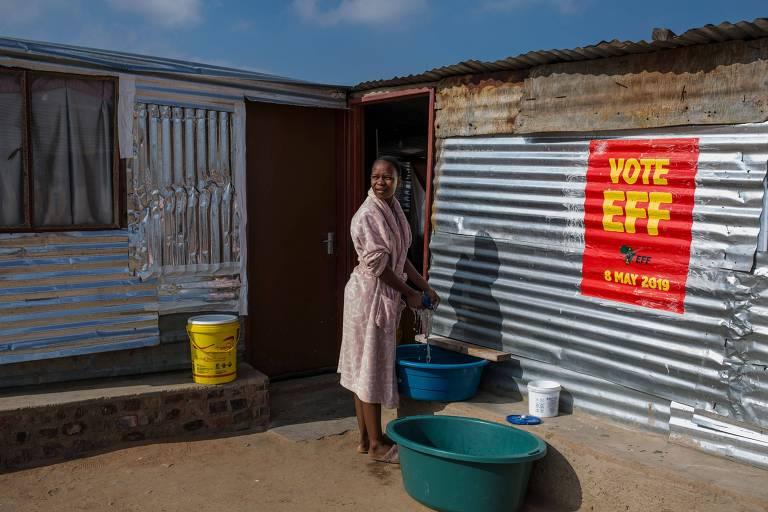 Didimatso Makgoka, 18, lava roupa em bacia do lado de fora de sua casa