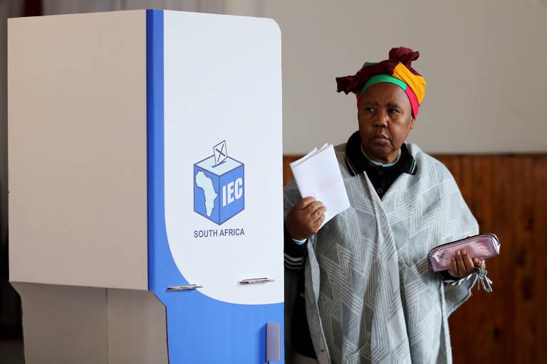 Mulher segura cédula de papel nas mãos em frente à urna de votação