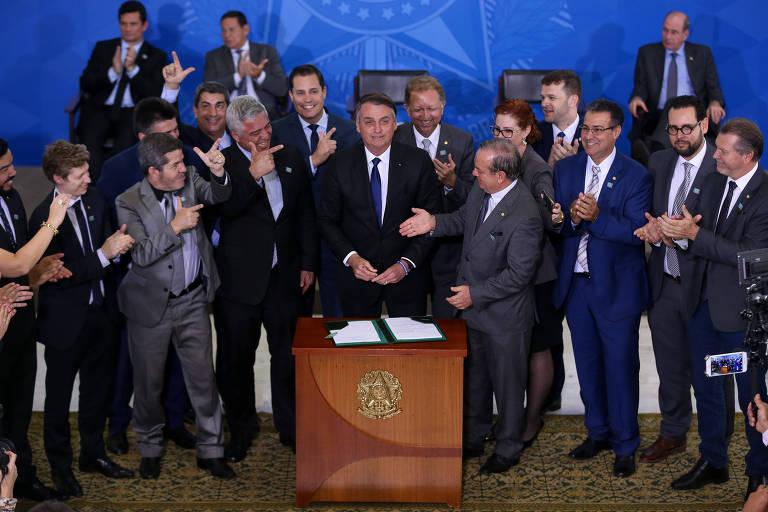 O presidente Jair Bolsonaro durante assinatura de decreto que flexibiliza posse e porte de armas, cercado de parlamentares favoráveis à medida