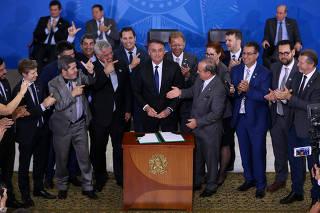 Parlamentares fazem o símbolo da arma com os dedos ao lado de Bolsonaro