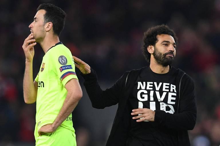 """Com a camisa escrita """"nunca desista"""", Mohamed Salah passa pelo espanhol Sergio Busquets, do Barcelona, após a goleada do Liverpool"""