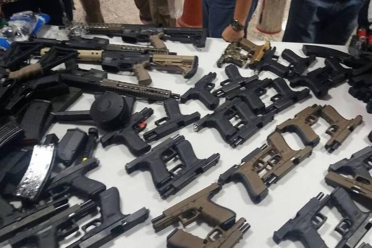 Mesa com diversas pistolas e outras armas de fogo que foram apreendidas