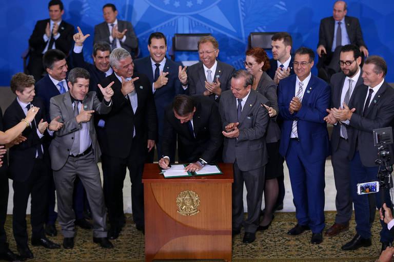 Jair Bolsonaro (centro) durante cerimônia em que assinou decreto com novas regras relacionadas ao porte de armas e munições