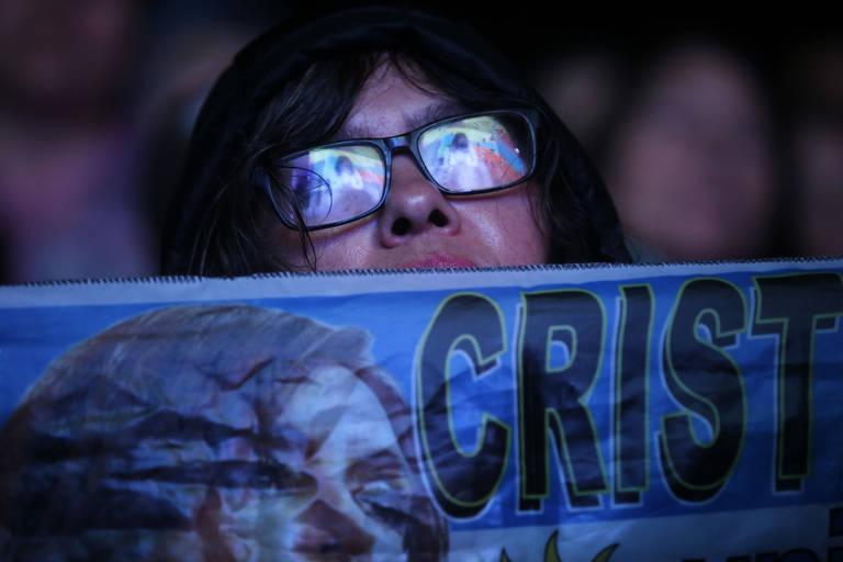 Mulher tem rosto parcialmente coberto com faixa com imagem de cristina; ela usa oculos, e as lentes refletem a imagem de cristina, que fala no palco a sua frente