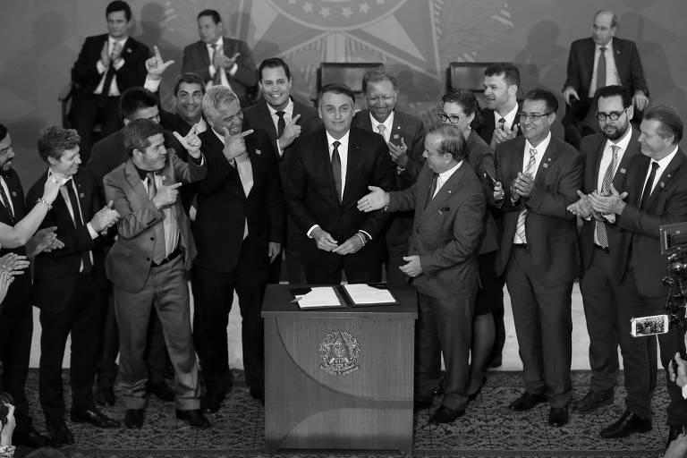 Jair Bolsonaro (centro) e congressistas durante cerimônia em que o presidente assinou decreto com novas regras relacionadas ao porte de armas