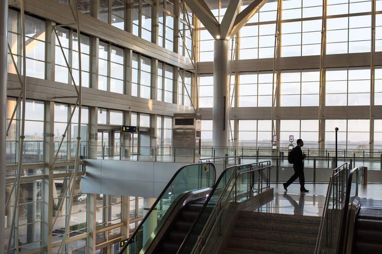 A foto mostra a sombra de uma pessoa passando em frente ao topo de uma escada rolante. As paredes de vidro, deixam a luz do dia entrar e iluminar todo o saguão