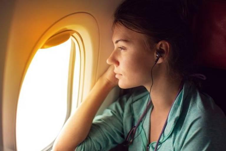 Mulher olha através de janela de avião
