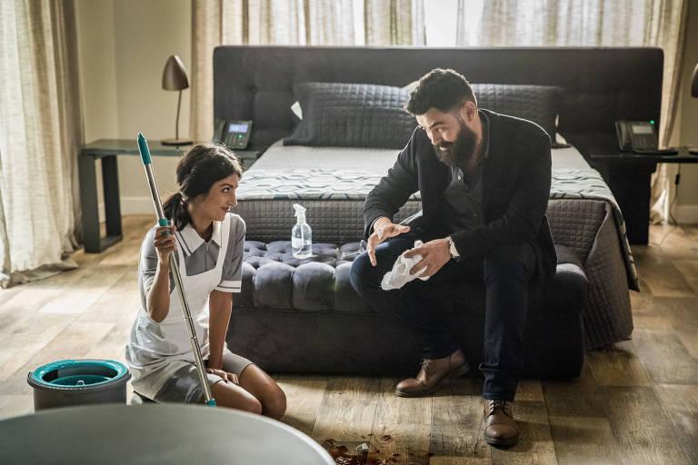 Camila (Anaju Dorigon) entra com seu kit de limpeza, e Paul (Carmo Dalla Vechia) a convida para ir ao bar do hotel