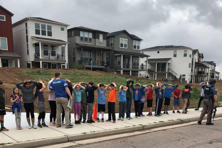 crianças em fila com as mãos na cabeça enquanto adulto percorre a fila