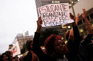 A university student holds a sign during a protest against the education policies of Brazilian President Jair Bolsonaro's government in Sao Paulo, Brazil
