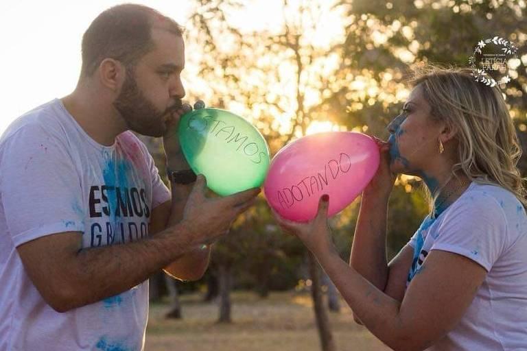 """Casal enche balões com as palavras """"estamos adotando"""""""