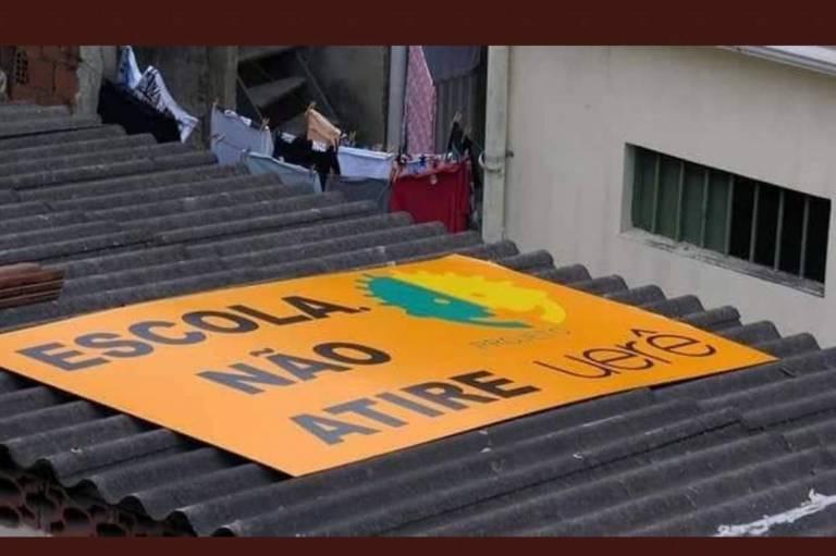 Placa no teto da escola Uerê, na Maré, pedindo que não atirem na unidade